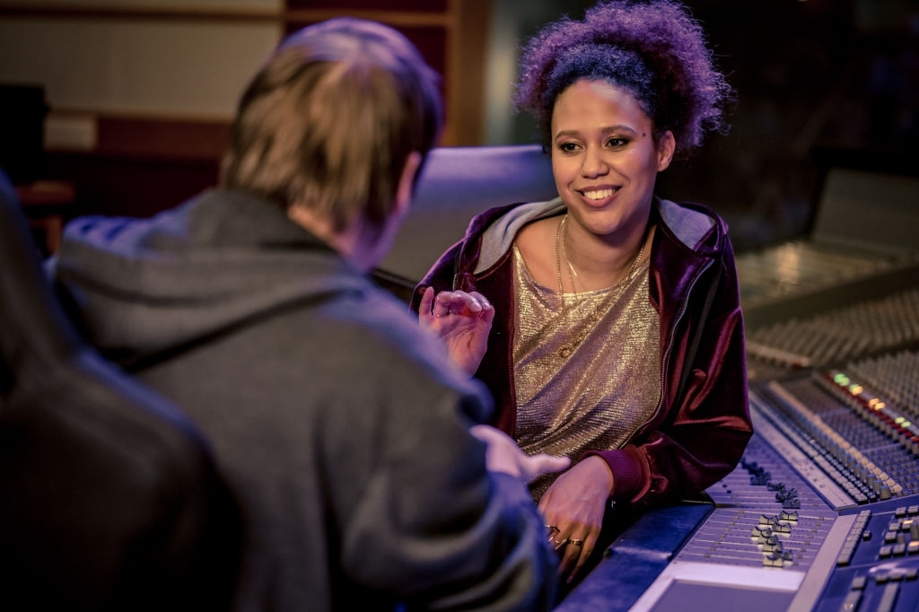Smiling young adult mixed race woman sitting in recording studio and chatting with colleague. Music, arts and entertainment concept.